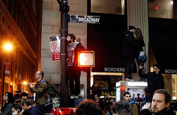 A couple kiss as they stand on top of a telephone booth as they are surrounded by demonstrators affiliated with the Occupy Wall St. movement near Zuccotti Park in New York November 15, 2011 (Reuters / Lucas Jackson)
