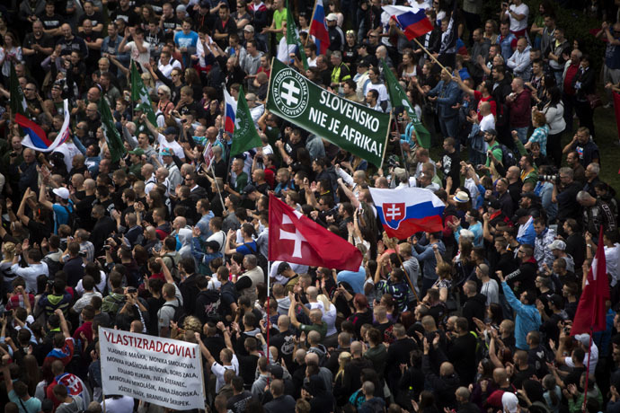 "Participants wave flags and hold a banner reading ""Slovakia is not Africa"" during an anti-immigration rally organised by an initiative called ""Stop Islamisation of Europe"" and backed by the far-right ""People's Party-Our Slovakia"" on June 20, 2015 in Bratislava, Slovakia. (AFP Photo/Vladimir Simicek)"