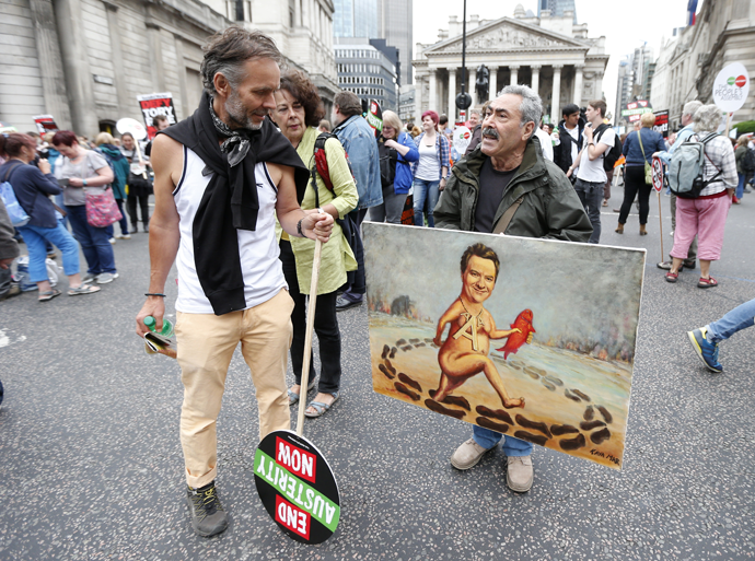 A demonstrator looks at an artist holding a painting showing Britain's Chancellor George Osborne, during an anti-austerity protest in London, Britain June 20, 2015. (Reuters / Suzanne Plunkett)