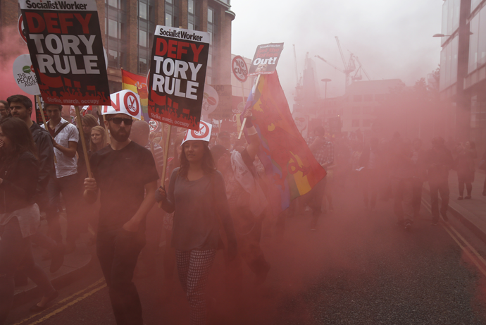 Demonstrators march through red smoke during an anti-austerity protest in central London, Britain June 20, 2015. (Reuters / Peter Nicholls)
