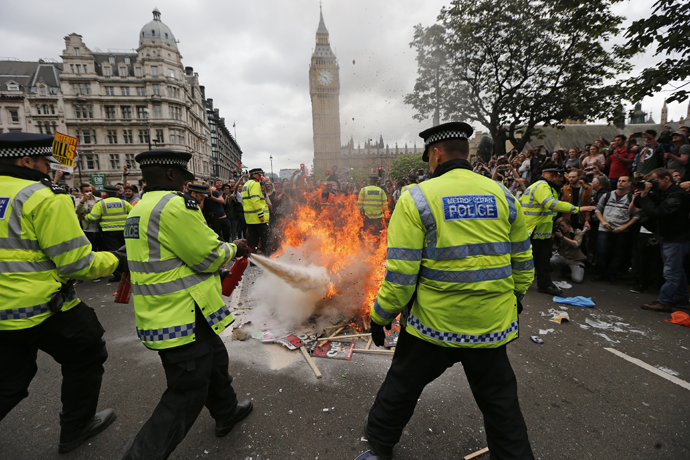 Police extinguish burning placards in front of parliament during an anti-austerity protest in central London, Britain June 20, 2015. (Reuters / Suzanne Plunkett)