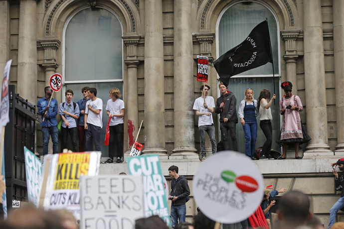 Demonstrators stand on a window ledge during an anti-austerity protest in central London, Britain June 20, 2015. (Reuters / Suzanne Plunkett)