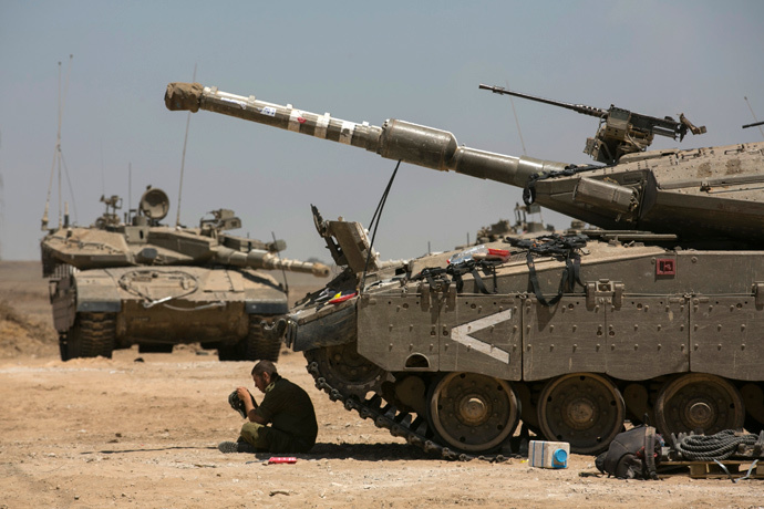 An Israeli soldier sits next to tanks at a staging area near the border with the Gaza Strip August 21, 2014. (Reuters / Baz Ratner)