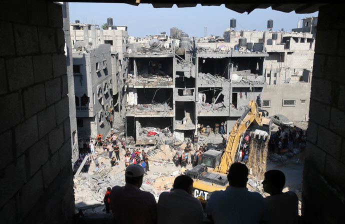 Palestinians watch as rescue workers search for victims under the rubble of a house, which witnesses said was destroyed in an Israeli air strike that killed three senior Hamas military commanders, in Rafah in the southern Gaza Strip August 21, 2014. (Reuters / Ibraheem Abu Mustafa)
