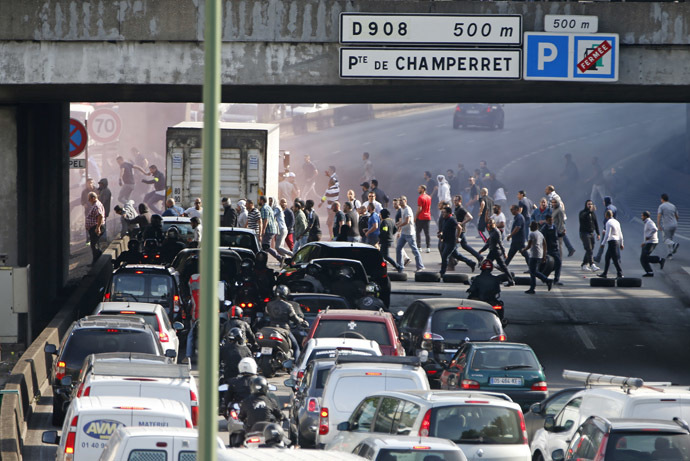 French taxi drivers, who are on strike, block the traffic on the Paris ring road during a national protest against car-sharing service Uber, in Paris, France, June 25, 2015. (Reuters / Charles Platiau)