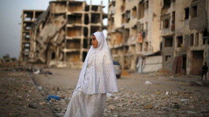 A Palestinian girl stands near residential buildings that witnesses said were heavily damaged by Israeli shelling during a 50-day war last summer, in Beit Lahiya town in the northern Gaza Strip May 25, 2015. (Reuters/Suhaib Salem)