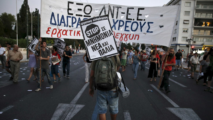 "A protester carries a placard that reads ""Stop to new and old bailouts"" during an anti-bailout demonstration in Athens, Greece June 25, 2015. (Reuters / Alkis Konstantinidis)"