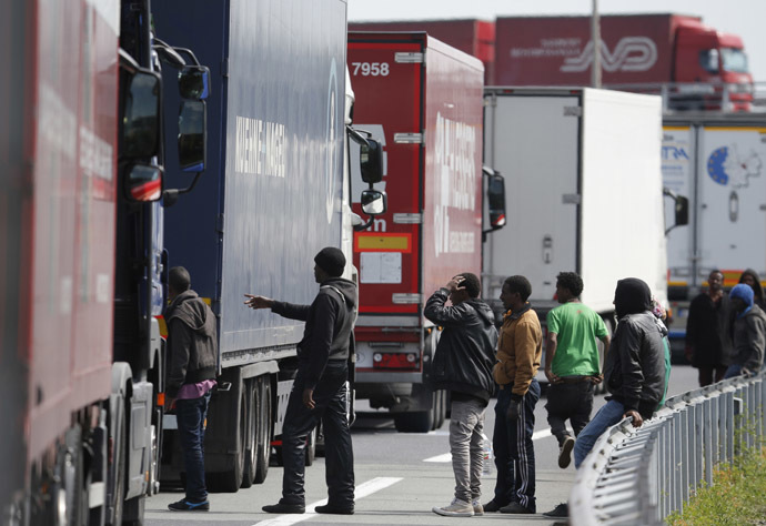 A group of migrants gather near a line of lorries waiting on the motorway which leads to the Channel Tunnel terminal in Calais, northern France, June 24, 2015. (Reuters / Christian Hartmann)