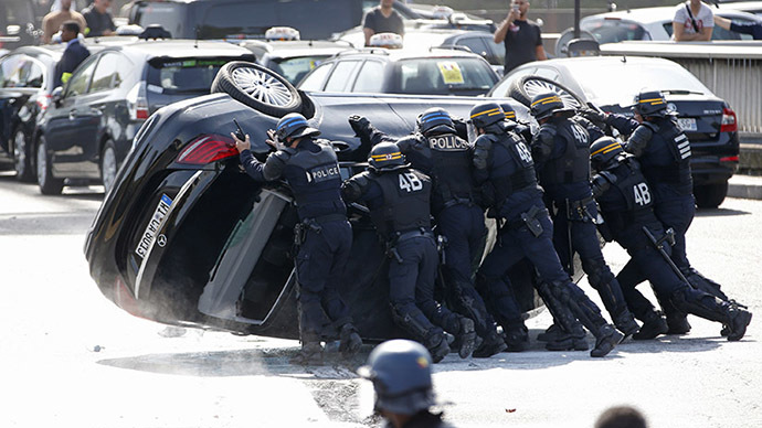 French riot police push an overturned car as striking French taxi drivers demonstrate at the Porte Maillot to block the traffic on the Paris ring road during a national protest against car-sharing service Uber, in Paris, France, June 25, 2015. (Reuters / Charles Platiau)