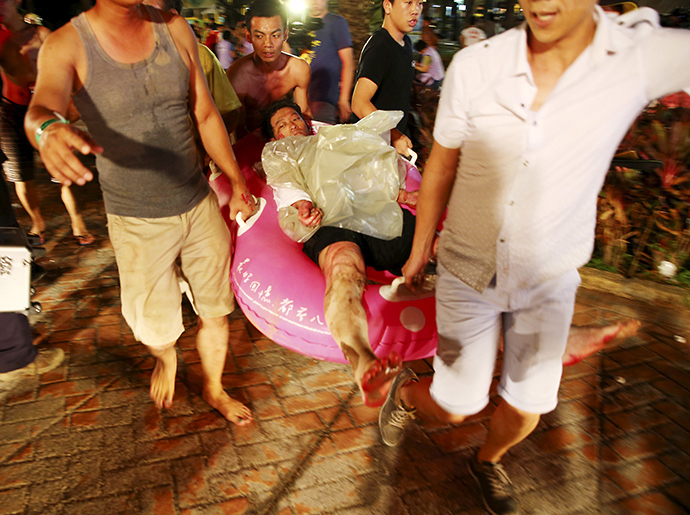 People carry an injured victim from an accidental explosion during a music concert at the Formosa Water Park in New Taipei City, Taiwan, June 27, 2015 (Reuters / Chen Bo)