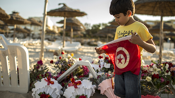 A boy holds a Tunisian flag as he stands near bouquets of flowers laid at the beachside of the Imperiale Marhabada hotel, which was attacked by a gunman in Sousse, Tunisia, June 27, 2015 (Reuters / Zohra Bensemra)