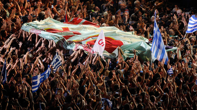 Protestors hold a giant flag in front of the parliament building during an anti-austerity rally in Athens, Greece, July 3, 2015. (Reuters / Jean-Paul Pelissier)