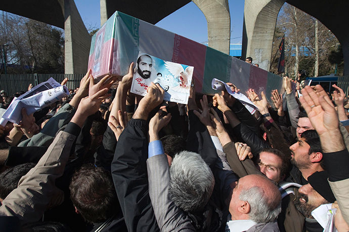 Iranian worshippers carry a picture and coffin of Iranian nuclear scientist Mostafa Ahmadi-Roshan, who was killed in a bomb blast in Tehran on January 11, during his funeral after Friday prayers in Tehran January 13, 2012 (Reuters / Morteza Nikoubazl)
