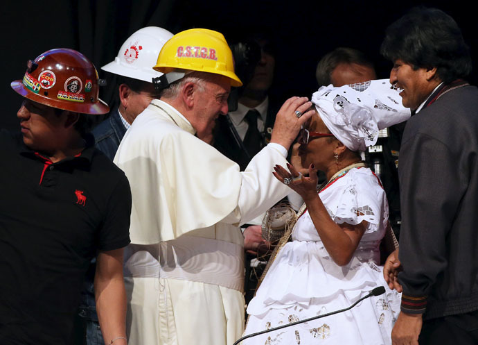 Pope Francis, wearing a helmet, blesses a woman as Bolivian President Evo Morales (R) looks on, during a World Meeting of Popular Movements in Santa Cruz, Bolivia, July 9, 2015. (Reuters/Alessandro Bianchi)