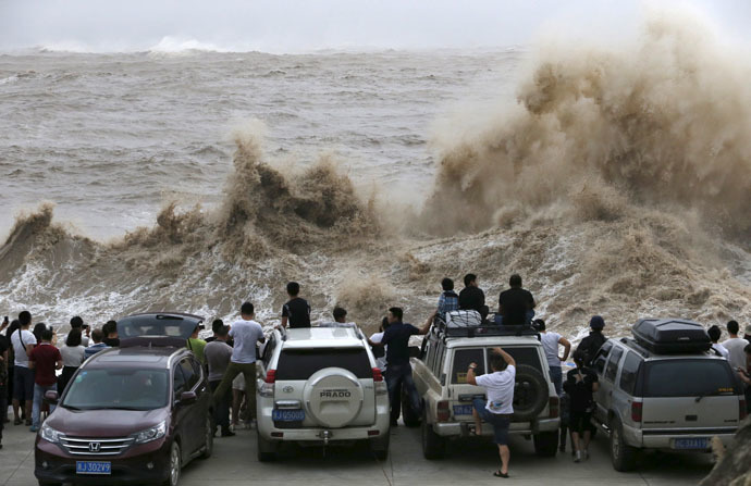 People look on as waves, under the influence of Typhoon Chan-hom, hit the shore in Wenling, Zhejiang province, China, July 10, 2015. (Reuters/William Hong)