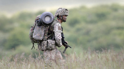A British soldier on exercise walks across an area of Salisbury Plain, near to Westdown Camp, Britain, June 18, 2015. (Reuters/Peter Nicholls)