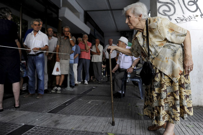 A pensioner (R) arrives at a National Bank branch to receive part of her pension at the city of Thessaloniki, Greece (Reuters/Alexandros Avramidis)