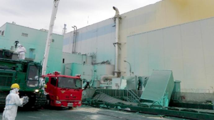 """Fukushima operator says """"sorry"""" as workers erect protective cap"""