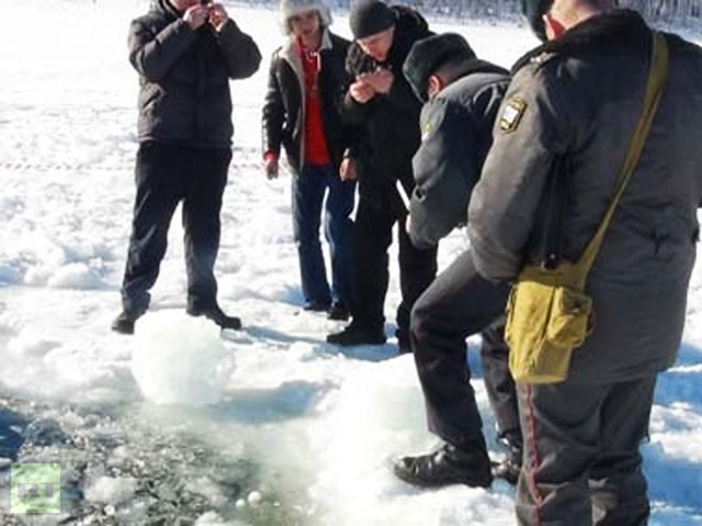 Police officers, environmentalists and EMERCOM experts at the site of a meteorite hit in the Chelyabinsk Region. Small 0.5-1 cm pieces of black matter resembling rock were found around the ice hole caused by the meteorite. Photo courtesy of the press service of the Interior Ministry′s Main Directorate for the Chelyabinsk Region.(RIA Novosti)