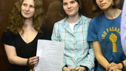 Ekaterina Samutsevich (C), Maria Alyokhina (L) and Nadezhda Tolokonnikova (R) show the court's verdict as they sit in a glass-walled cage in Moscow court on Agust 17, 2012 (AFP Photo / STR)