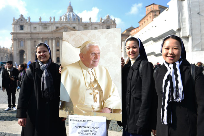 Asian nuns hold a portrait of Pope Benedict XVI on St Peter's square after the Angelus prayer led by Pope Benedict XVI from the window of his appartments.(AFP Photo / Gabriel Bouys)