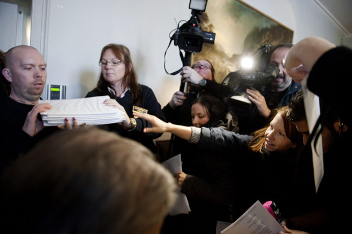 Reporters get a copy of the Svea Appeals Court verdict in the Pirate Bay case in Stockholm on November 26, 2010. (AFP Photo / Jessica Gow)