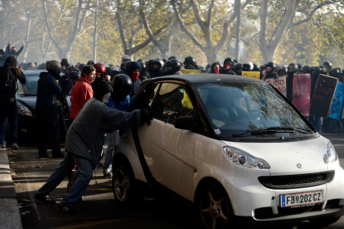 Demonstrators push a car during a protest on a day of mobilisation against austerity measures by workers in southern Europe on November 14, 2012 in Rome (AFP Photo / Filippo Monteforte)