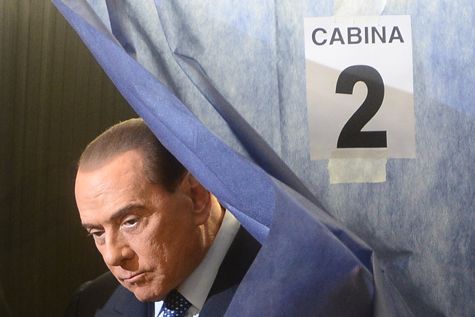 Italian former Prime Minister Silvio Berlusconi leaves the voting booth before casting his ballot at a polling station on February 24, 2013 in Milan (AFP Photo / Olivier Morin)
