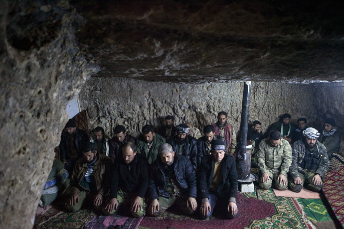 Rebels pray inside a cave in the village of Kfarruma in the flashpoint Syrian province of Idlib near the border with Turkey, on February 10, 2013. (AFP Photo/Daniel Leal-Olivas)