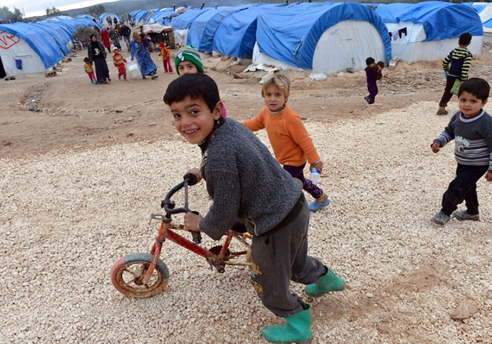 Syrian children play outside their tents at the refugee camp of Qah along the Turkish border in the village of Atme in the northwestern province of Idlib, on February 7, 2013. (AFP Photo / Aamir Qureshi)