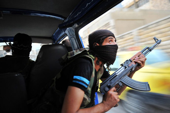 Syrian rebels hunt for snipers after attacking the municipality building in the city center of Selehattin, near Aleppo, on July 23, 2012, during fights between rebels and Syrian troops. (AFP Photo / Bulent Kilic)
