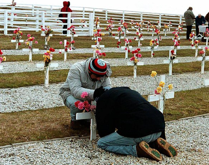 Relatives of Argentine soldiers who died during Argentina's 1982 war over the Falkland Islands decorate tombs at a cemetery. (AFP Photo / Angeline Montoya)