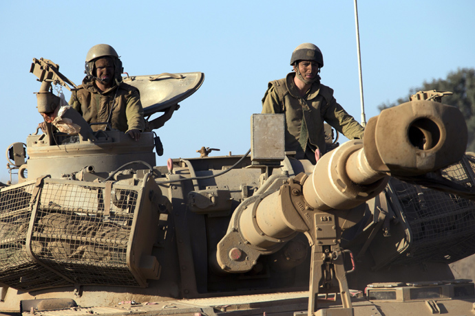 Israeli soldiers ride on top of a mobile artillery vehicle as it drives through sandy terrain during a military exercise in the Israeli-occupied Golan Heights, north of Israel on Sepetember 19, 2012 (AFP Photo / Jack Guez)