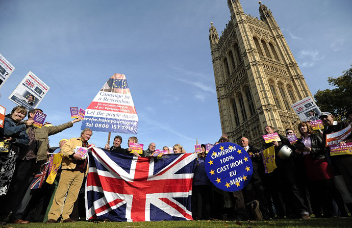 United Kingdom Independence Party (UKIP) supporters hold Union Jack flags and placards as they take part in a demonstration outside the Houses of Parliament in central London on October 24, 2011. (AFP Photo / Carl Court)