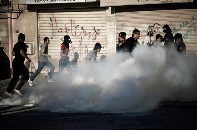Anti-regime Bahraini protestors run for cover from tear gas and bird shots fired by riot police during clashes on February 22, 2013. (AFP Photo / MohammedAl-Shaikh)
