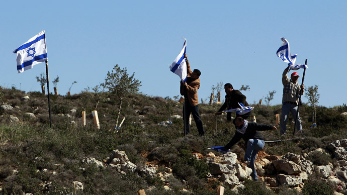Palestinian activists remove Israeli flags during a protest against what they say is Israel's denial of access to their farmland, in the village of Khirbet Zakaria, near the settlement bloc of Gush Etzion (Reuters/Ammar Awad)