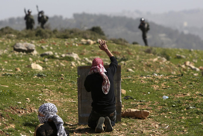 A Palestinian protester gestures in front of Israeli border police during clashes at a weekly protest against Jewish settlements, in the West Bank village of Nabi Saleh (Reuters/Mohamad Torokman)