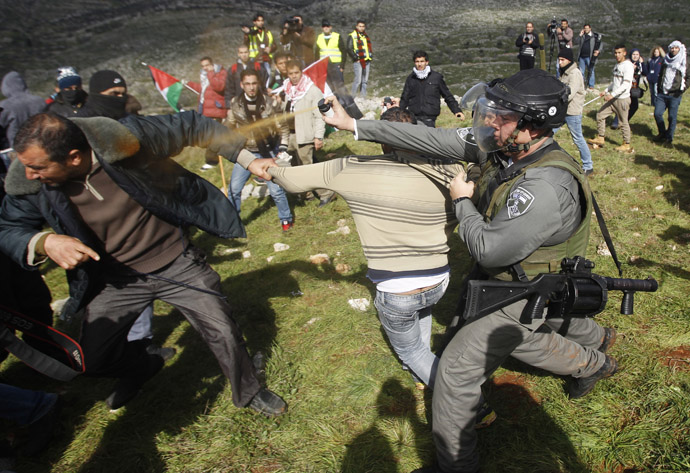 An Israeli border police officer uses pepper spray to disperse Palestinian activists after the group set up tents and makeshift structures in protest against a nearby Jewish settlement in the West Bank village of Burin, south of Nablus (Reuters/Mohamad Torokman)