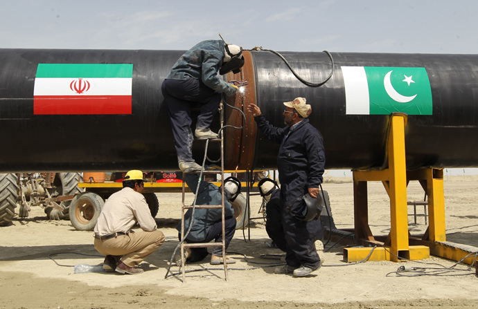 Iranians work on a section of a pipeline (on with are sticked Iranian and Pakistanese national flags) after the project was launched during a ceremony with presidents of Iran and Pakistan on March 11, 2013 in the Iranian border city of Chah Bahar (AFP Photo / Atta Kenare)