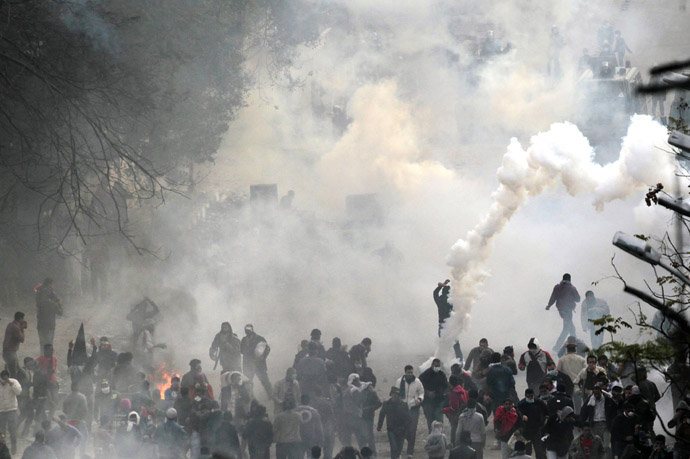 Protesters run from tear gas thrown by police forces during clashes near the Interior Ministry in Cairo, February 3, 2012. (Reuters/Mohamed Abd El-Ghany)