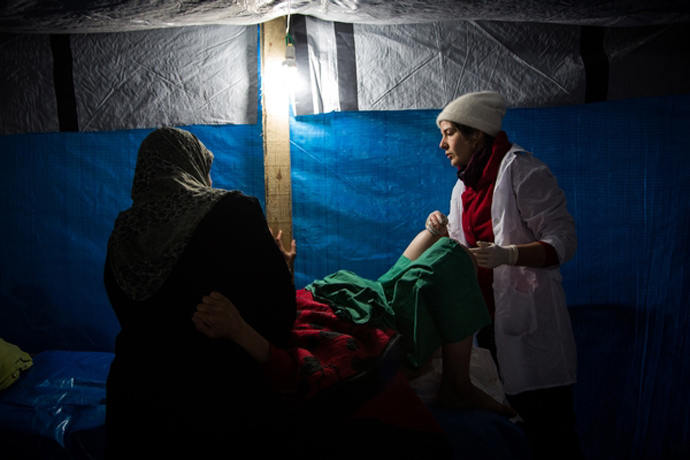 Midwife Cathy Janssens calms and assists patient Raida Dumyati as she attempts to deliver her baby by natural means at the MSF hospital in Northern Syria (photo by Nicole Tung)