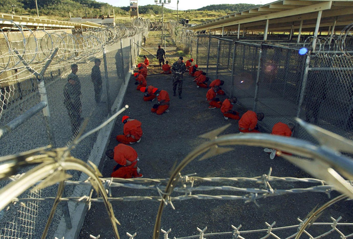 Detainees in orange jumpsuits sit in a holding area under the watchful eyes of military police during in-processing to the temporary detention facility at Camp X-Ray of Naval Base Guantanamo Bay in this January 11, 2002 file photograph. (Reuters/Stringer/Files)