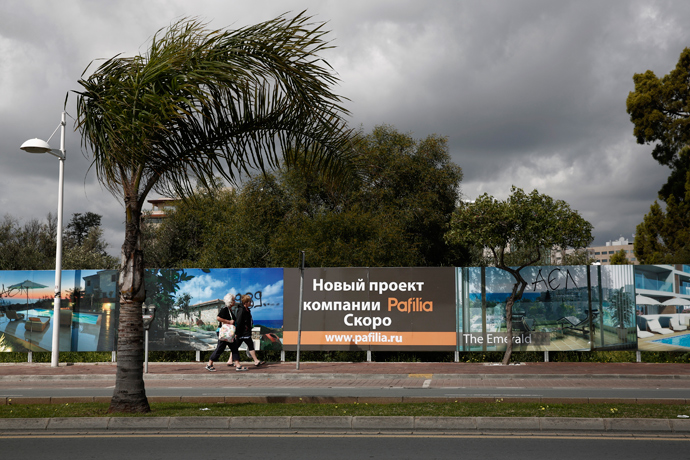 Two women make their way alongside Russian advertisements about a property development in Limassol, a coastal town in southern Cyprus (Reuters / Yorgos Karahalis)