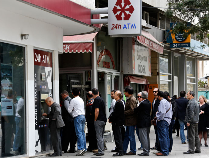 People queue up to make transactions at an ATM outside a branch of Laiki Bank in Nicosia.(Reuters / Yannis Behrakis)