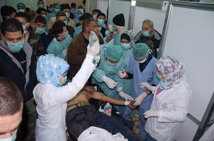 Medics and other masked people attend to a man at a hospital in Khan al-Assal in the northern Aleppo province, as Syria's government accused rebel forces of using chemical weapons for the first time on March 19, 2013. (AFP Photo / SANA)