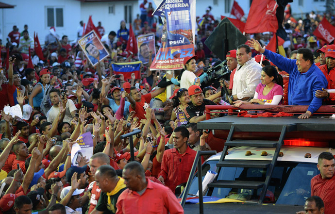 Venezuelan President Hugo Chavez (R) waves to supporters during a campaign rally in Barquisimeto, Lara state on October 2, 2012. (AFP Photo/Juan Barreto)