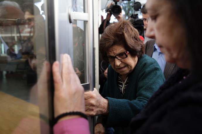 A woman holds the door of a Laiki bank branch in the Cypriot capital, Nicosia, on March 28, 2013, as people queue up outside waiting for the bank to open after an unprecedented 12-day lockdown (AFP Photo)