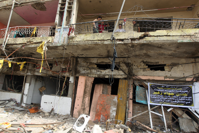 Iraqi stand on the balcony of a damaged building the day after twin car bombs in the Karrada area of the capital Baghdad on August 1, 2012 (AFP Photo / Ahmad Al-Rubaye)