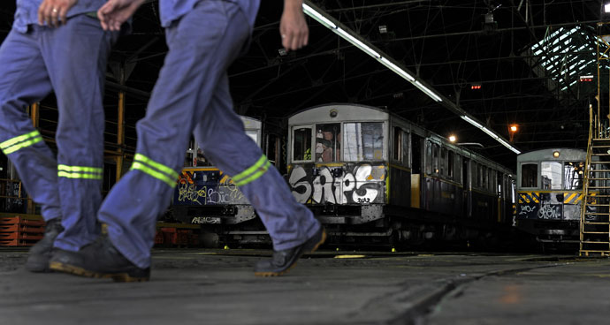 Workers walk next to the historic wagons of La Brugeoise at the garage El Polvorin, in the neighborhood of Caballito, Buenos Aires.(AFP Photo / Alejandro Pagni)