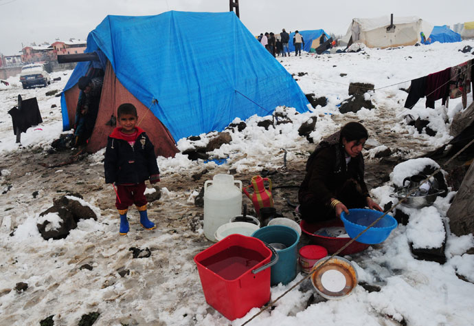 A child watches a woman washing a bassin at the Syrian refugee camp 5km from Diyarbakir, on the the way between Diyarbakir and Mardin, after snowfall, on January 9, 2013.(AFP Photo / Stringer)